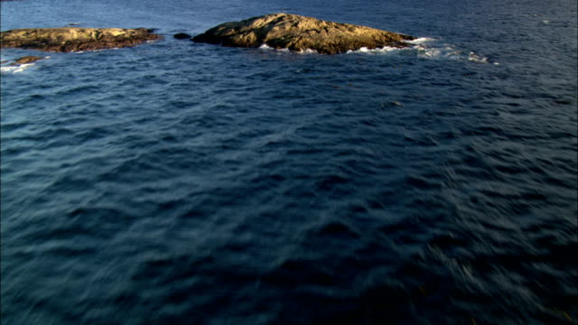 Waves wash around small rocky islands and the wooded coast of British Columbia.