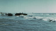 Weapons carrier and truck driving along beach beached LCVP in the shallows soldiers on the beach unloading LCVP