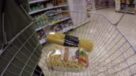 Wearable camera POV shot of carbohydrates and other foods being added to a shopping basket at a large supermarket in the UK.
