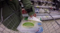 Wearable camera POV shot of dairy products being placed into a metal basket at a large supermarket in the UK.