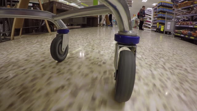 Wearable camera POV shot of the wheels of a shopping trolley as it is wheeled around the food aisles of a large UK supermarket.