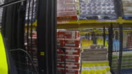 Wearable camera shot showing a forklift vehicle being used to place a pallet onto shelving at a large food distribution warehouse in the UK.