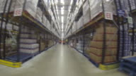 Wearable camera POV shot showing long rows of shelving as seen from a forklift vehicle at a food distribution warehouse in the UK.