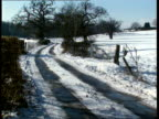 Weather UNITED Snowy lane with trees either side PULL OUT to show fields of snow GV Field of snow