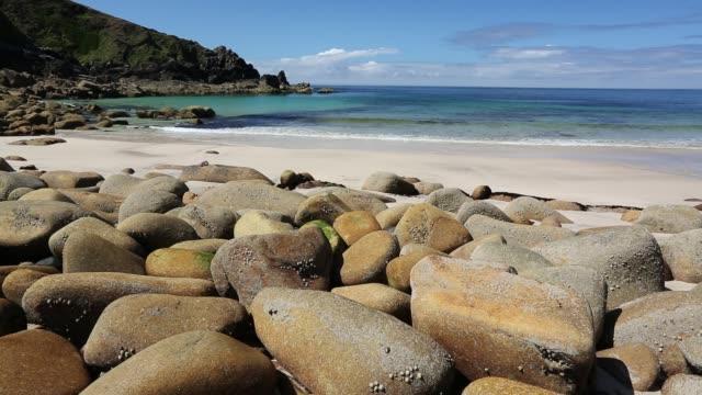 Weathered granite boulders on the beach at Porthmeor Cove, on Cornwall's North Coast, UK.