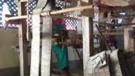 A weaver operates a wooden handloom to produce Eri silk at a mill in Udalgudi Assam A weaver is seen through threads of Eri silk as he operates a...