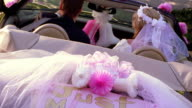 CANTED REAR VIEW wedding couple driving away in 'just married' convertible car
