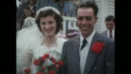 1954 HOME MOVIE Wedding couple exiting church, rice thrown, couple posing for picture, wedding party / Regina, Saskatchewan