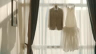 Wedding Dress and Suit Hanging in Front of Window