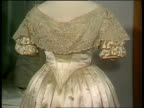 Wedding dress ENGLAND London Museum MS ZOOM dresses as two girls adjust CS Princess Charlotte's dress PULL BACK CS Bodice of Queen Victoria dress...