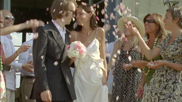 SLO MO, MS, CU, Wedding guests throwing flower petals on just married couple, Chateau du Parc, Saint Ferme, France