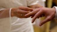 Ehering ist auf Bräutigam während sich die finger Zeremonie