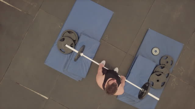 Weightlifting overhead press with barbell, aerial view