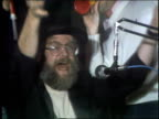 Weird Al Yankovic among a group of people dance around playing kazoos and other toy instruments as Dr Demento introduces his radio show in the studio...