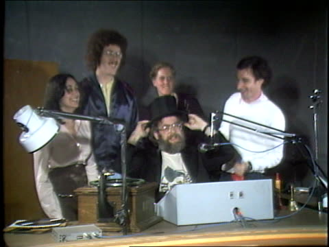 Weird Al Yankovic among a group of people dance around playing kazoos and other toy instruments as Dr Demento ends his radio show in the studio at...