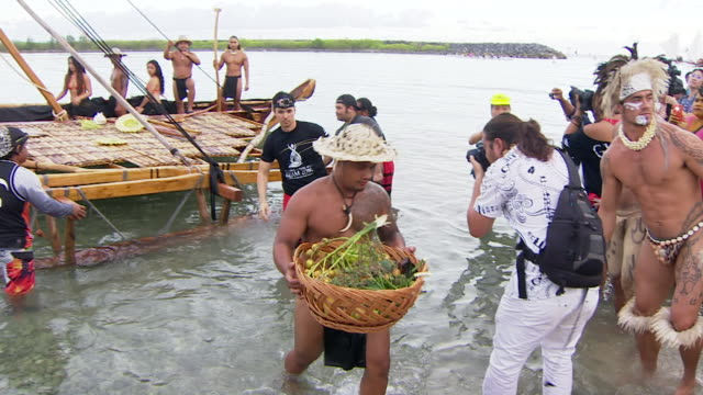 Welcome ceremony of traditional sailing vessels arriving for 12th Pacific Arts Festival in Guam with some crew disembarking carrying food