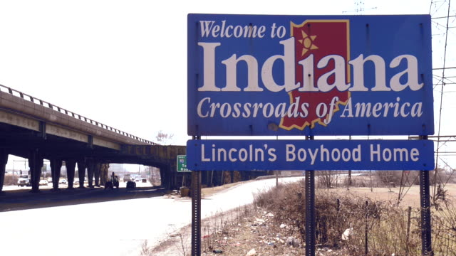 A welcome road sign greets travelers along an empty stretch of highway leading into the state of Indiana