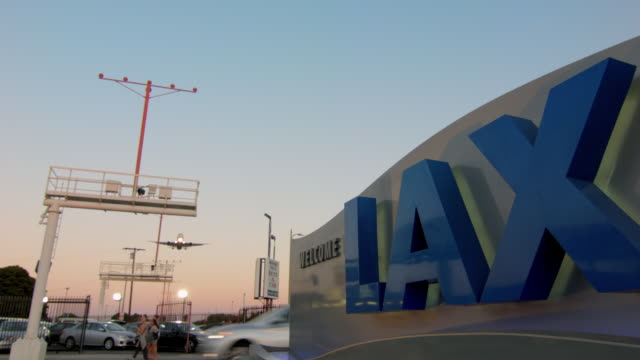 'Welcome to LAX' sign in foreground with jet airliner flying overhead on approach to landing, early evening