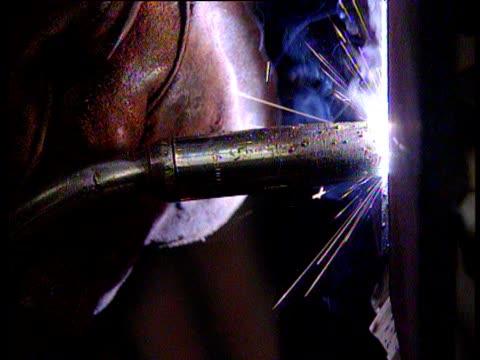 Welders at work performing TIG welding sparks flying past welders wearing boiler suits and welder's masks for protection; Kvaerner Shipyard Govan
