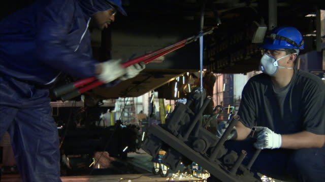 Welders remove components from a train car.
