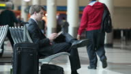 MS Well dressed young businessman using tablet device inside airport / Minneapolis, Minnesota, United States