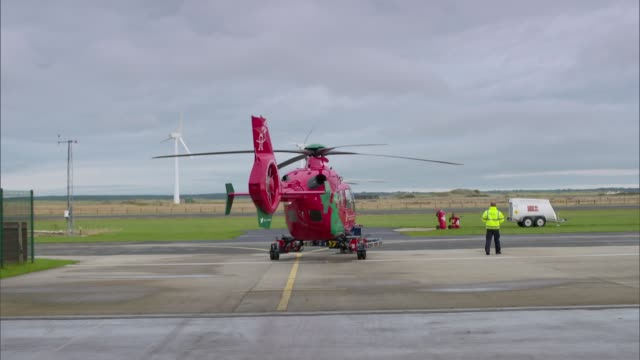 Welsh air ambulance general views EXT Air ambulance helicopter wheeled to helipad on trailer Helicopter wheeled from hangar Various views of Welsh...