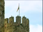 Welsh flag blowing in wind on top of Conwy Castle North Wales