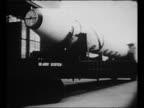 Wernher von Braun speaks with military official during satellite planning meeting / LS US Army JupiterC rocket moves past lying on trailer / crane...