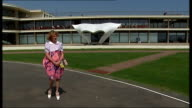 Bexhill EXT Grayson Perry dressed as alter ego 'Claire' posing in front of gallery wearing white platform shoes and pink dress