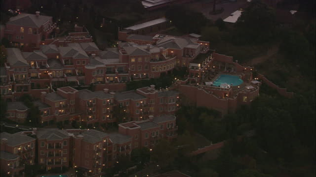 AERIAL WS Westcliff Hotel and swimming pool illuminated at night, Johannesburg, Gauteng, South Africa