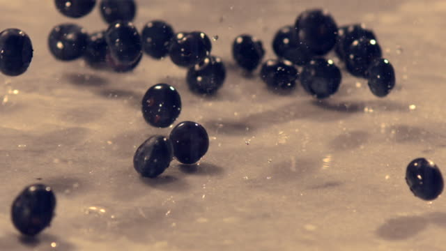 Wet blueberries falling onto marble surface (slow motion)