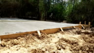 Wet concrete freshly poured in preparation for construction foundation.