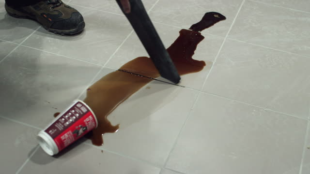 CU of wet dry vacuum sucking up spilled coffee