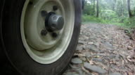 CU Wheel of 4x4 vehicle as it drives along dirt track.  (Branding visible on tyre)