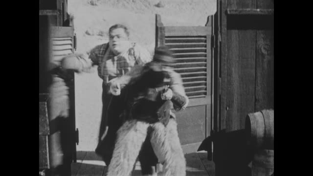 While avoiding being hunted by Native American Indians, Fatty Arbuckle runs inside the saloon knocking over Wild Bill Hiccup
