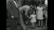 While holding a bouquet of roses actress Joan Fontaine poses with men a little girl curtsies / Fontaine kneels to talk with one / VS she sits in the...