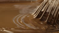 A whisk stirs smooth chocolate.