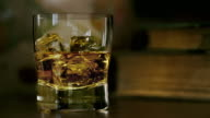 Whiskey pouring over ice in the study