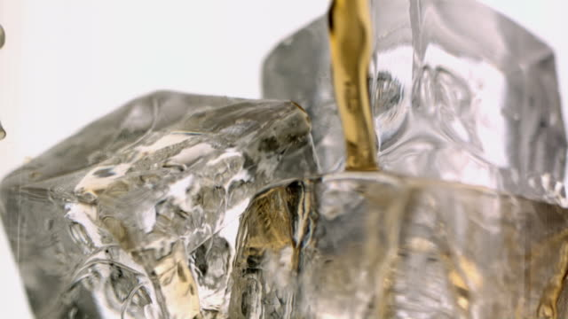 CU SLO MO Whisky being poured into glass over ice / New Jersey, USA