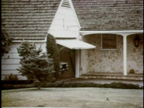 MONTAGE WS PAN White AMC Gremlin emerging from garage/ WS Gremlin stopping near gardening neighbor/ USA