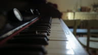 A white bird feather falls down slowly over the keys of an old piano