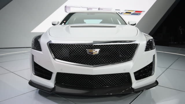 A white Cadillac CT5 sits on a rotating stage at the 2015 Detroit Auto Show in Detroit Michigan Close up shots of the Cadillac medallion and logo on...