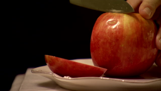 White ceramic plate on white counter top pair of unidentifiable male hands w/ black sleeves placing red apple onto plate using chef knife slicing...