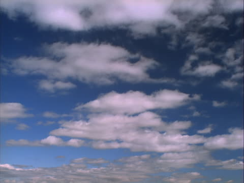 White clouds blowing across blue sky