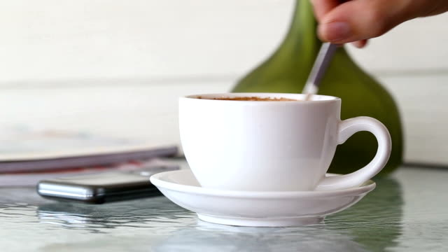 White coffee mug on glass table and hand of man stirring well and picked up to drink.