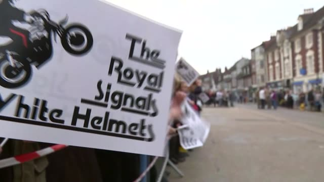 Dorset Blandford EXT Schoolchildren waving White Helmets flags / crowd on high street / White Helmets and trailer along high street past cheering...