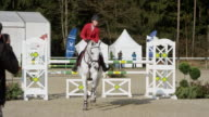 White horse with rider jumping over obstacles in sunshine