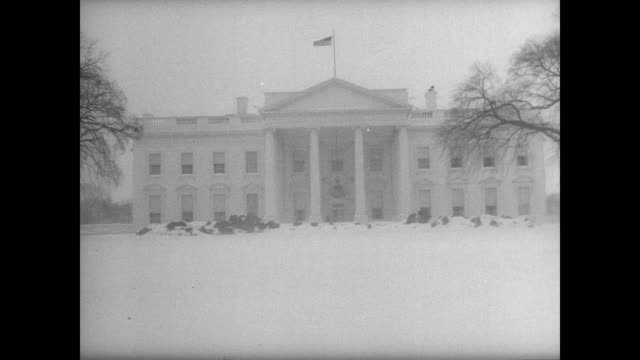 EXT White House blurred by snow / empty Lincoln Memorial / people struggling against the weather walking down the streets / slow traffic making its...