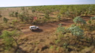 WS TS AERIAL White jeep through green woods with dried grass field / Karumba, Queensland, Australia