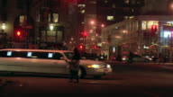 PAN A white limousine turning and driving past the entrance to the Plaza Hotel at night, with pedestrians and traffic / New York City, New York, United States